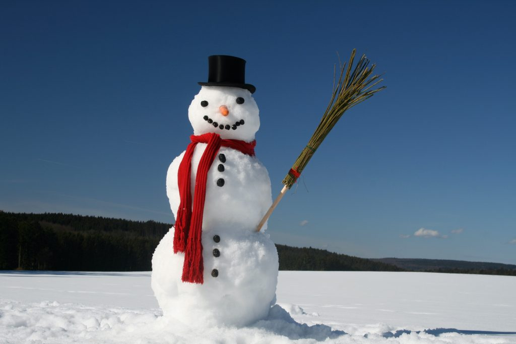 Snowman standing in the snow, in the middle of nowhere with black top hat, red scarf and a broom