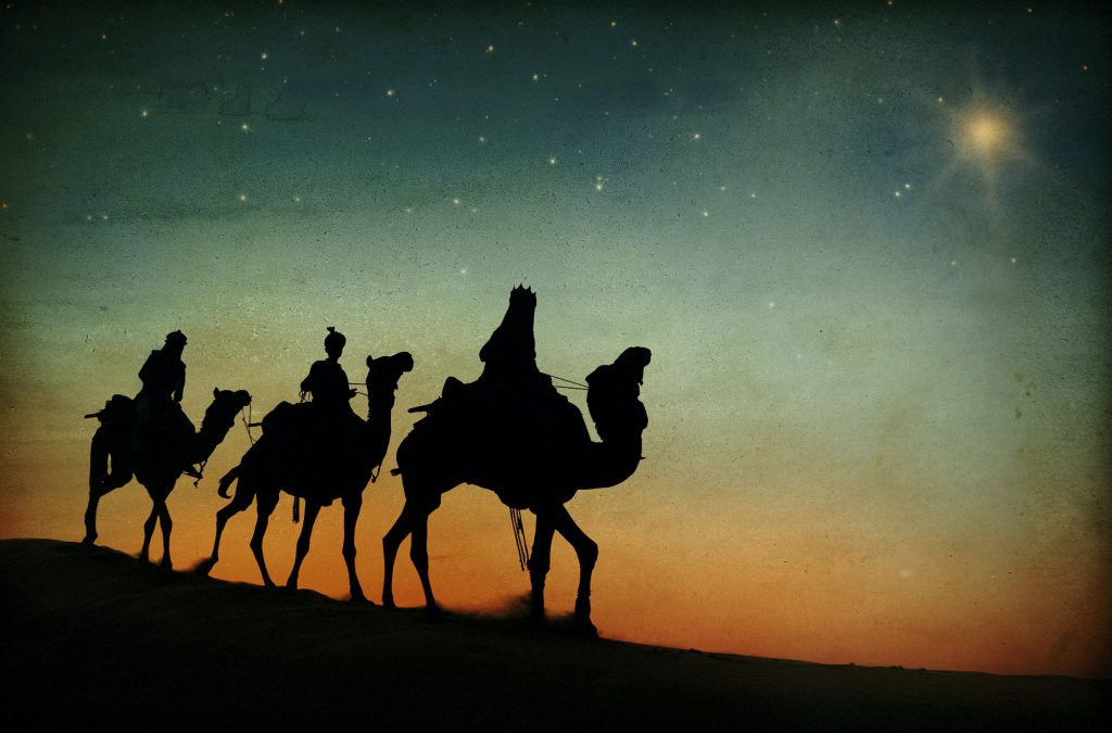 Dark silhouette of the three kings on camels following the star