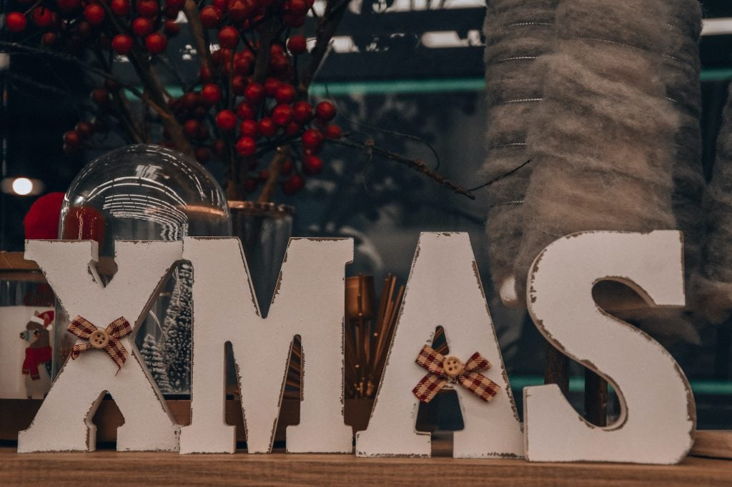 Big wooden letters in the color white spelling Xmas standing on a wooden shelf.