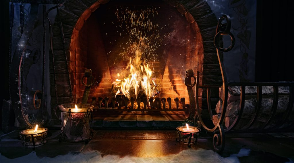 Yule log, open fire with tealights and firewood in front of the fireplace.