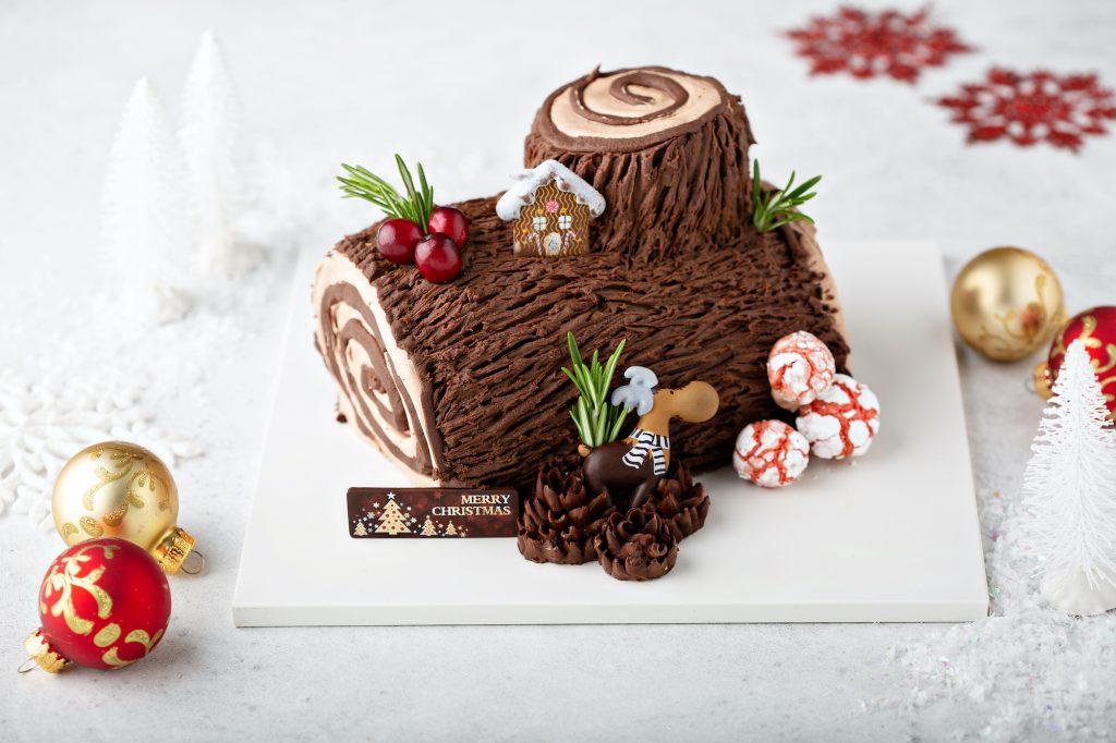 Christmas Yule log cake with edible sweet mushrooms and pine cones.